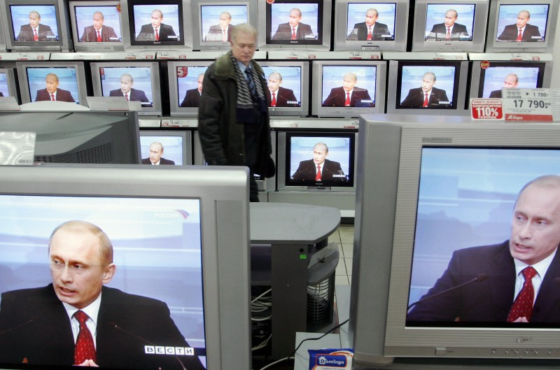 A man looks at TV sets, broadcasting live the annual press conference of the Russian President Vladimir Putin in an electronics store in Moscow on Jan. 31, 2006.  (Denis Sinyakov/AFP/Getty Images)