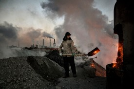 A Chinese worker loads coal into a furnace on November 3, 2016 in Inner Mongolia, China. (Kevin Frayer/Getty Images)