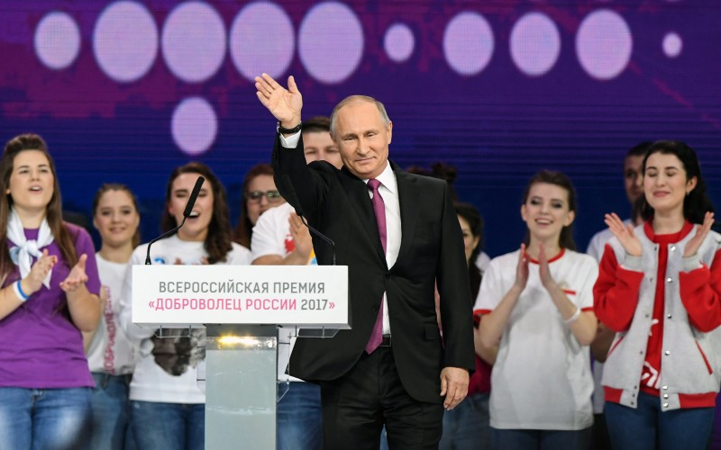 Russian President Vladimir Putin waves after delivering a speech at a forum of volunteers in Moscow on December 6, 2017. (KIRILL KUDRYAVTSEV/AFP/Getty Images)