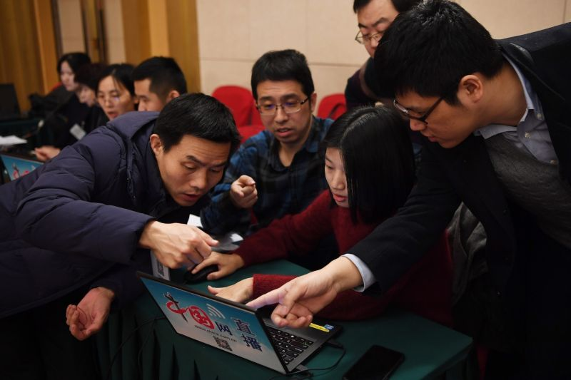 Journalists crowd around a laptop at the National People's Congress in Beijing on March 6.  (Greg Baker/AFP/Getty Images)