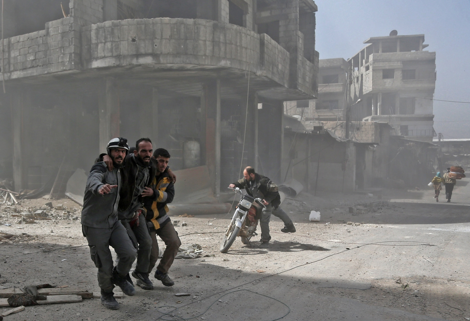 TOPSHOT - Volunteers from the Syrian civil defence help a man in Hamouria during Syrian government shelling on rebel-held areas in the Eastern Ghouta region on the outskirts of the capital Damascus on March 6, 2018. Heavy air strikes and clashes shook the Syrian rebel enclave of Eastern Ghouta, as France and Britain called for an emergency UN Security Council meeting on the escalating violence. / AFP PHOTO / ABDULMONAM EASSA        (Photo credit should read ABDULMONAM EASSA/AFP/Getty Images)