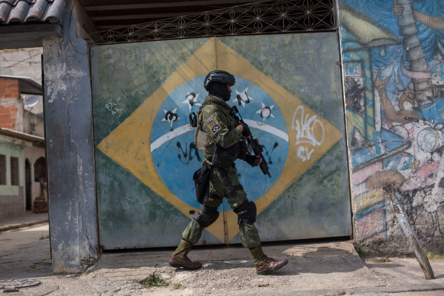 TOPSHOT - A soldier of the Armed Forces, backed by armoured vehicles, aircraft and heavy engineering equipment, takes part in an operation in the violence-plagued favela of Vila Kennedy, in Rio de Janeiro, Brazil, on March 7, 2018. The Brazilian army launched a new operation on a favela in Rio de Janeiro, the third since President Michel Temer ordered the military to take over the command of security in the whole of Rio state to fight organized crime. / AFP PHOTO / Mauro PIMENTEL        (Photo credit should read MAURO PIMENTEL/AFP/Getty Images)