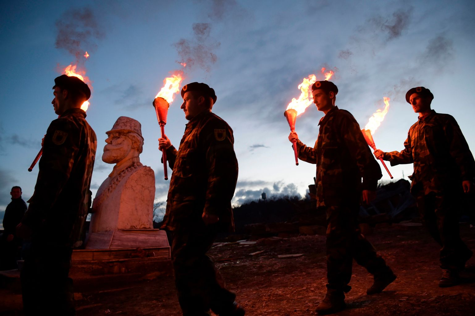 TOPSHOT - Kosovo Albanians dressed in military costumes carry torches during a bonfire ceremony marking the 20th anniversary of the killing of Kosovo Liberation Army (KLA) founding member and commander Adem Jashari, whose sculpture is seen rear left, on March 7, 2018 in Prekaz.  Jashari was among dozens of members of his family that were killed by Serb security forces in the village of Prekaz. / AFP PHOTO / Armend NIMANI        (Photo credit should read ARMEND NIMANI/AFP/Getty Images)