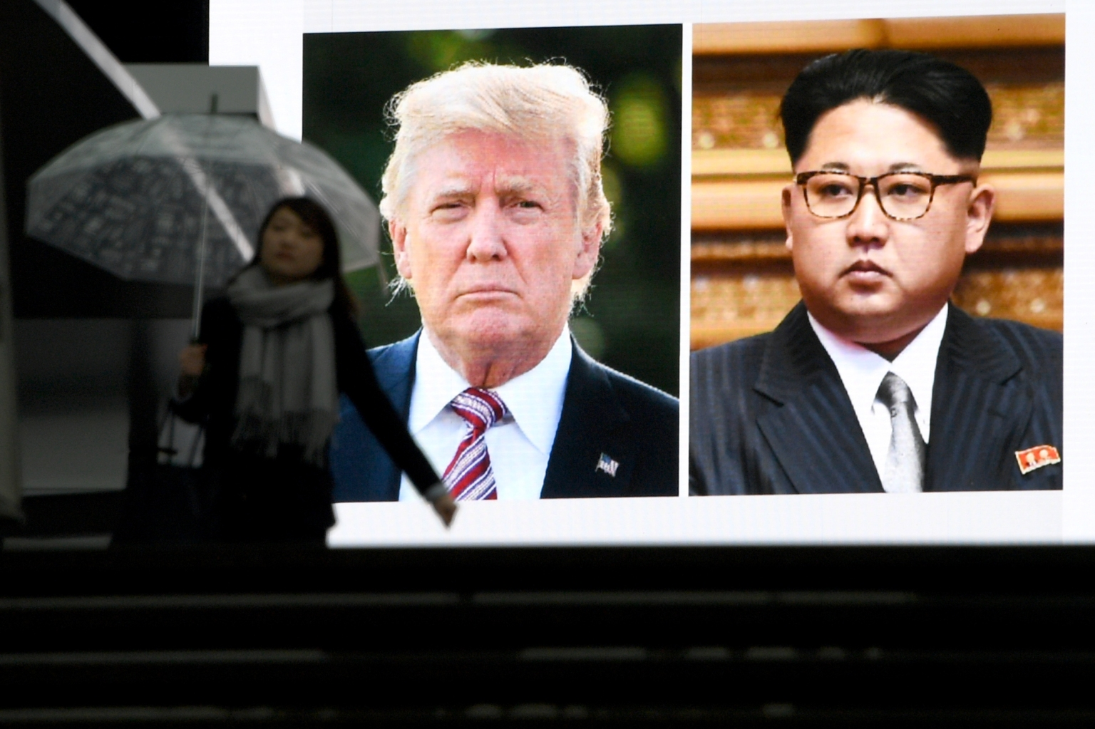 TOPSHOT - A pedestrian walks in front of a huge screen flashing a news report relating to US President Donald Trump and North Korean leader Kim Jong agreeing to meet for talks in Tokyo on March 9, 2018.   Japan's prime minister on March 9 welcomed the surprise announcement of a summit between US President Donald Trump and North Korea's Kim Jong Un by the end of May. / AFP PHOTO / Toshifumi KITAMURA        (Photo credit should read TOSHIFUMI KITAMURA/AFP/Getty Images)