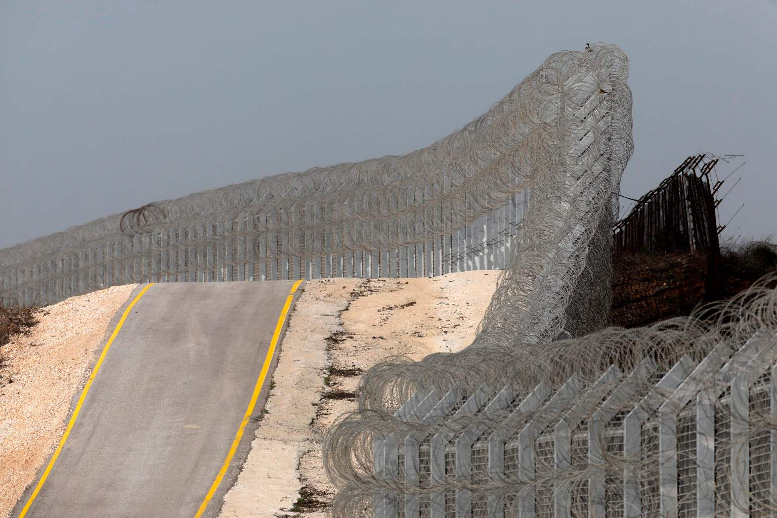 TOPSHOT - A picture taken on March 8, 2018 shows the border fence separating the Israeli-annexed Golan Heights and Syria, east of the Israeli settlement of Ramat Magshimim. / AFP PHOTO / MENAHEM KAHANA        (Photo credit should read MENAHEM KAHANA/AFP/Getty Images)