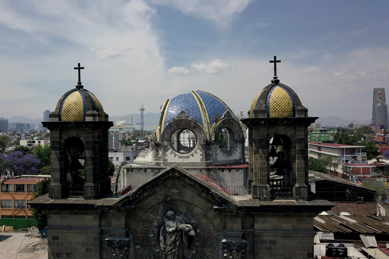 TOPSHOT - This aerial picture taken on March 18, 2018, shows a Catholic church which was damaged during the September 19, 2017 earthquake at Laredo street in Mexico City's Guerrero neighbourhood, undergoing reconstruction works. March 19, 2018 marks six months of a devastating quake. Mexican President Enrique Pena Nieto recently said that the two deadly earthquakes in September 2017 partially or totally damaged 184,000 homes, while 14,000 businesses and 16,000 schools were also affected. Reconstruction in central and southern Mexico following the quakes that killed a combined 465 people will require a $2.5 billion investment. / AFP PHOTO / Miguel TOVAR        (Photo credit should read MIGUEL TOVAR/AFP/Getty Images)