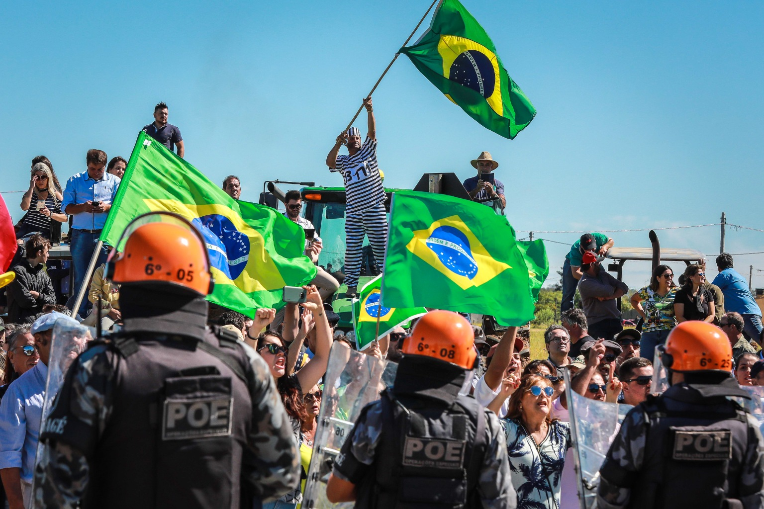 TOPSHOT - Riot police stand guard between opponents of former Brazilian President (2003-2010) Luiz Inacio Lula da Silva and a group of supporters (out of frame), in Bage, south of Brazil, where Lula arrived for a political gathering on March 19, 2018, just days before a court decision that could lead him to jail for corruption. Lula was convicted in 2017 and sentenced to nine and a half years in prison for accepting a luxury apartment from a construction company involved in a wide-ranging corruption probe that uncovered a web of kickbacks, bribes and slush funds involving high-level politicians from almost every party and throughout the business world. His lawyers appealed, but the conviction was upheld unanimously in January 2018 by a regional federal court in Porto Alegre, which increased the prison term to 12 years and one month. / AFP PHOTO / Itamar AGUIAR        (Photo credit should read ITAMAR AGUIAR/AFP/Getty Images)