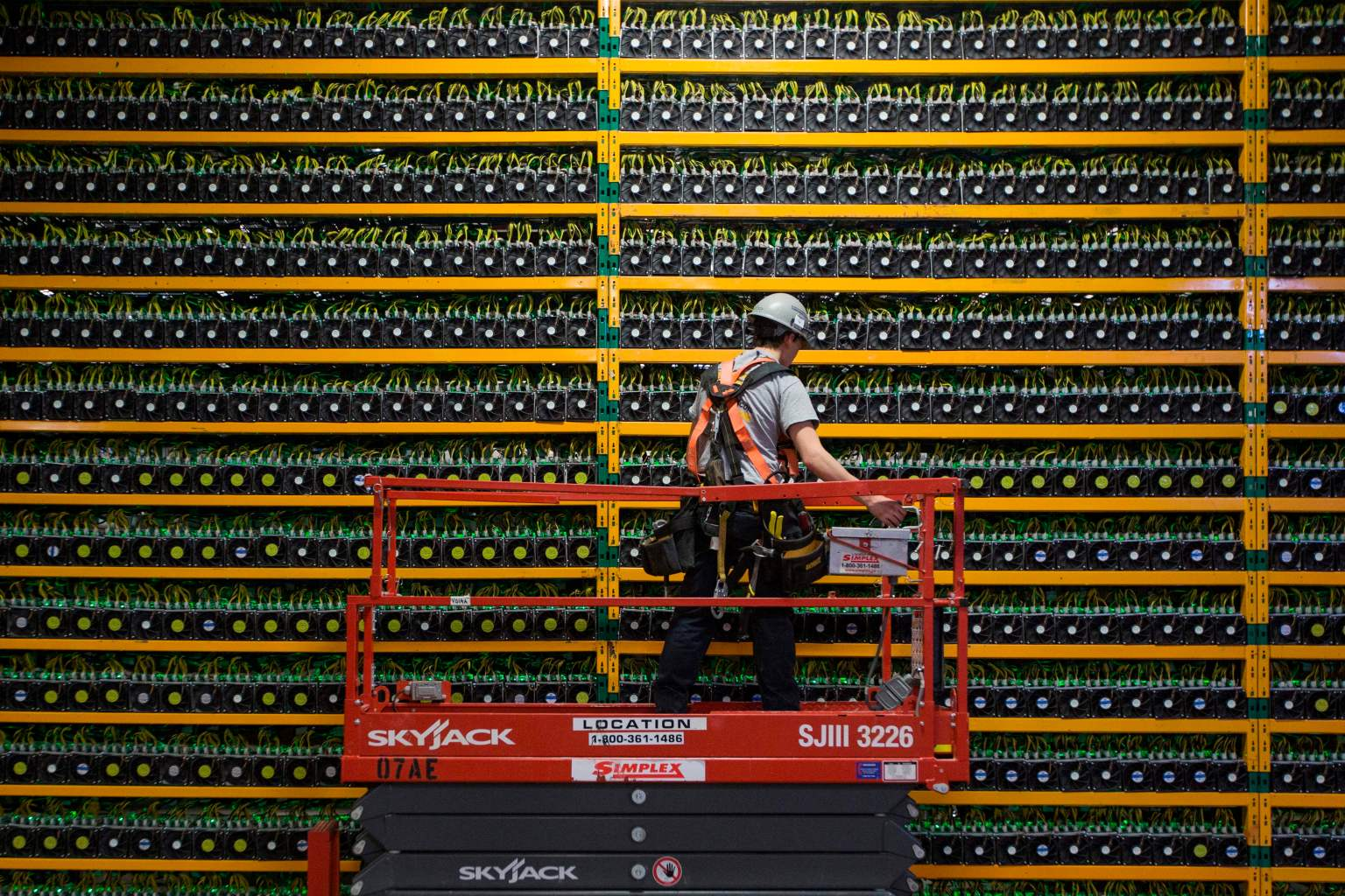 TOPSHOT - A technician inspects the backside of bitcoin mining at Bitfarms in Saint Hyacinthe, Quebec on March 19, 2018. Bitcoin is a cryptocurrency and worldwide payment system. It is the first decentralized digital currency, as the system works based on the blockchain technology without a central bank or single administrator. / AFP PHOTO / Lars Hagberg        (Photo credit should read LARS HAGBERG/AFP/Getty Images)