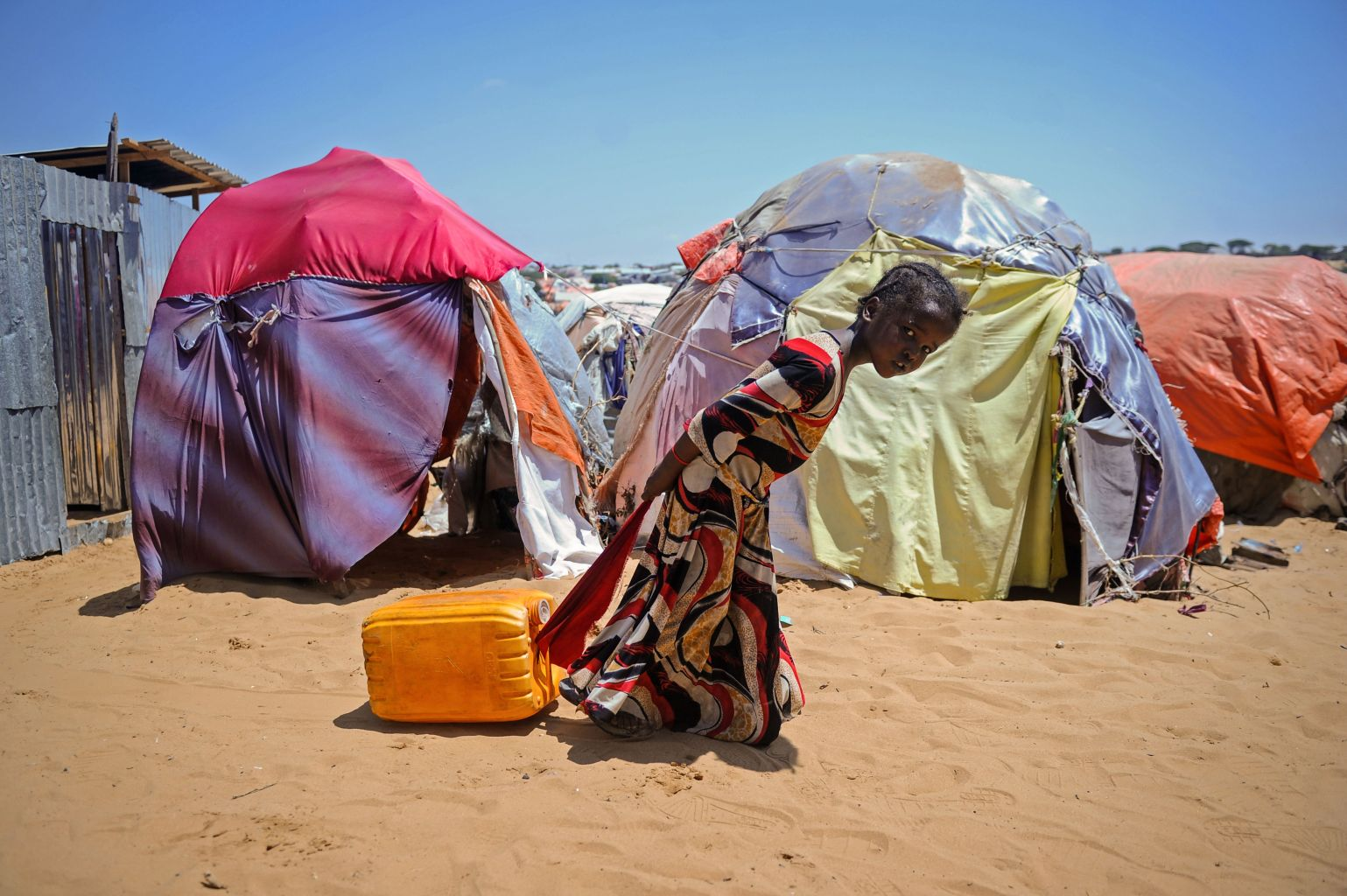 """TOPSHOT - A Somali girl drags a jerrycan filled with water from a well at the Tawakal IDP camp on the outskirts of Mogadishu, Somalia, on March, 21, 2018. World Water Day, on March 22, 2018, calls attention on the importance of water, with this year's theme """"Nature for Water""""  exploring nature-based solutions to the water challenges we face in the 21st century. / AFP PHOTO / Mohamed ABDIWAHAB        (Photo credit should read MOHAMED ABDIWAHAB/AFP/Getty Images)"""