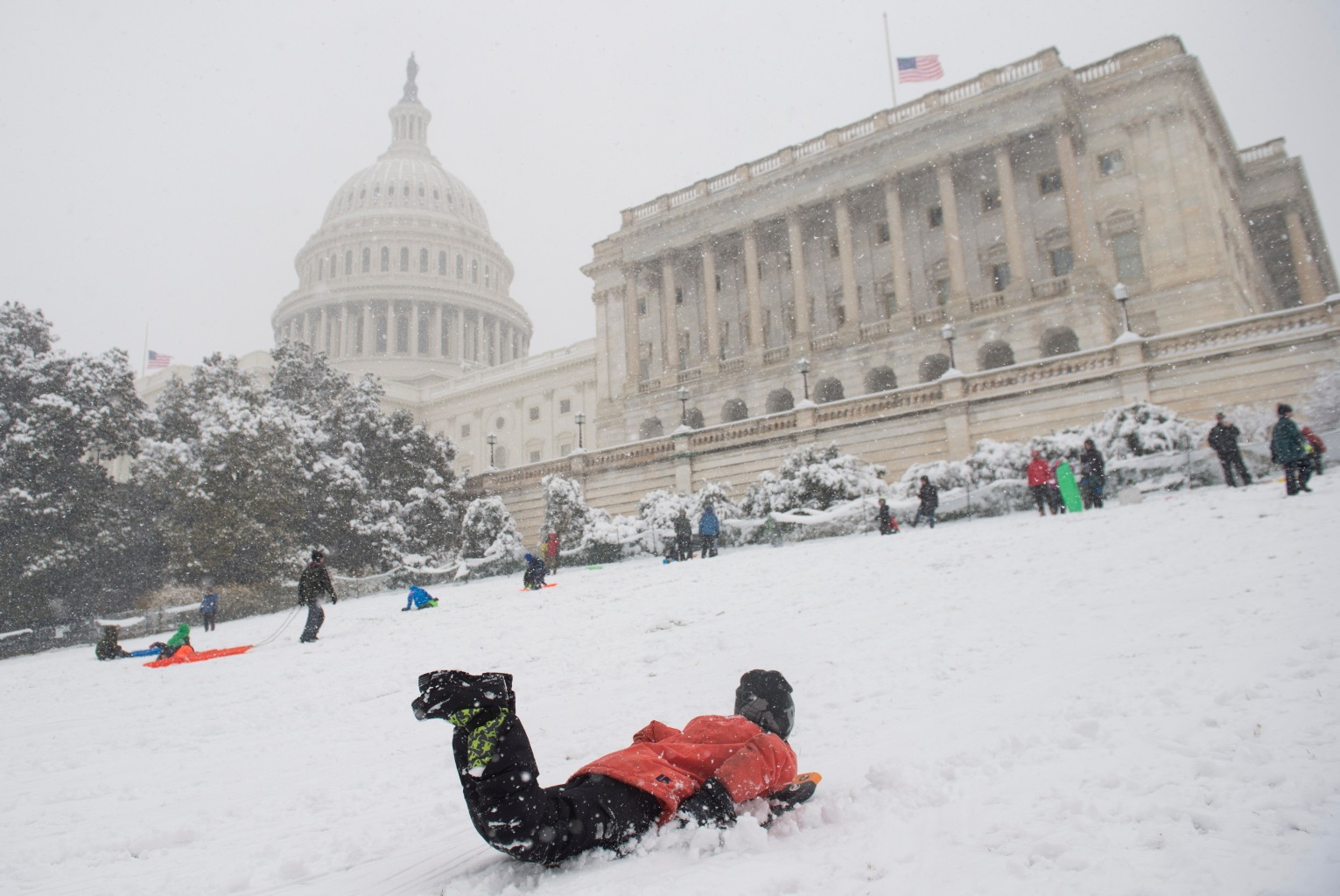 TOPSHOT - Children sled at the US Capitol during a snow storm in Washington, DC, March 21, 2018. The fourth Noreaster in less than three weeks, Winter Storm Toby, is throwing a fresh blanket of snow just as spring begins. The storm caused heavy damaged in the south with hail, high winds and tornadoes. / AFP PHOTO / SAUL LOEB        (Photo credit should read SAUL LOEB/AFP/Getty Images)
