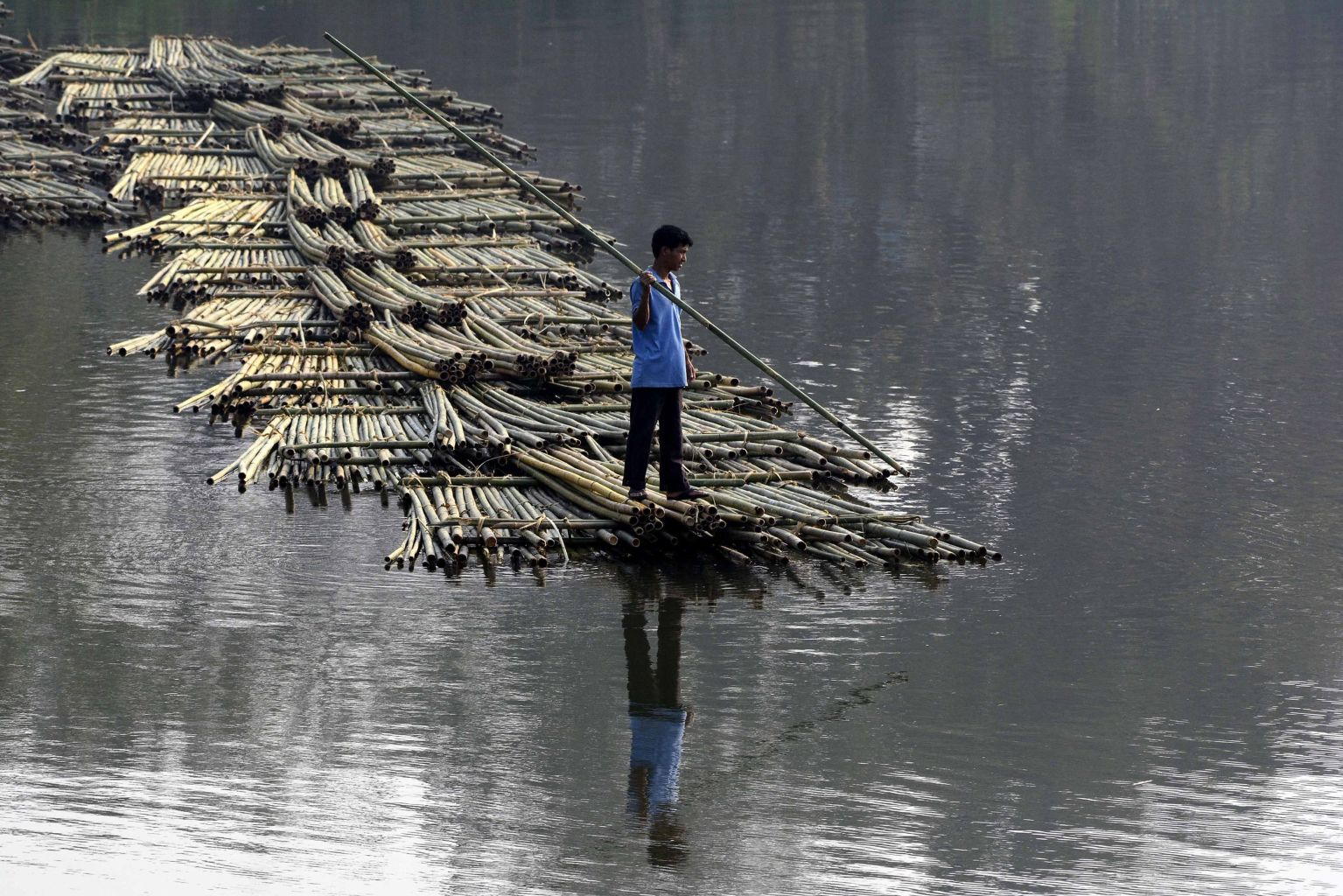 TOPSHOT - An Indian labourer pushes heaps of bamboo on a river to be sold at a floating market -- and set to be used in the construction industry -- in Chakmaghat, some 56km north of Agartala, the capital of northeastern state of Tripura, on March 22, 2018. / AFP PHOTO / Arindam DEY        (Photo credit should read ARINDAM DEY/AFP/Getty Images)