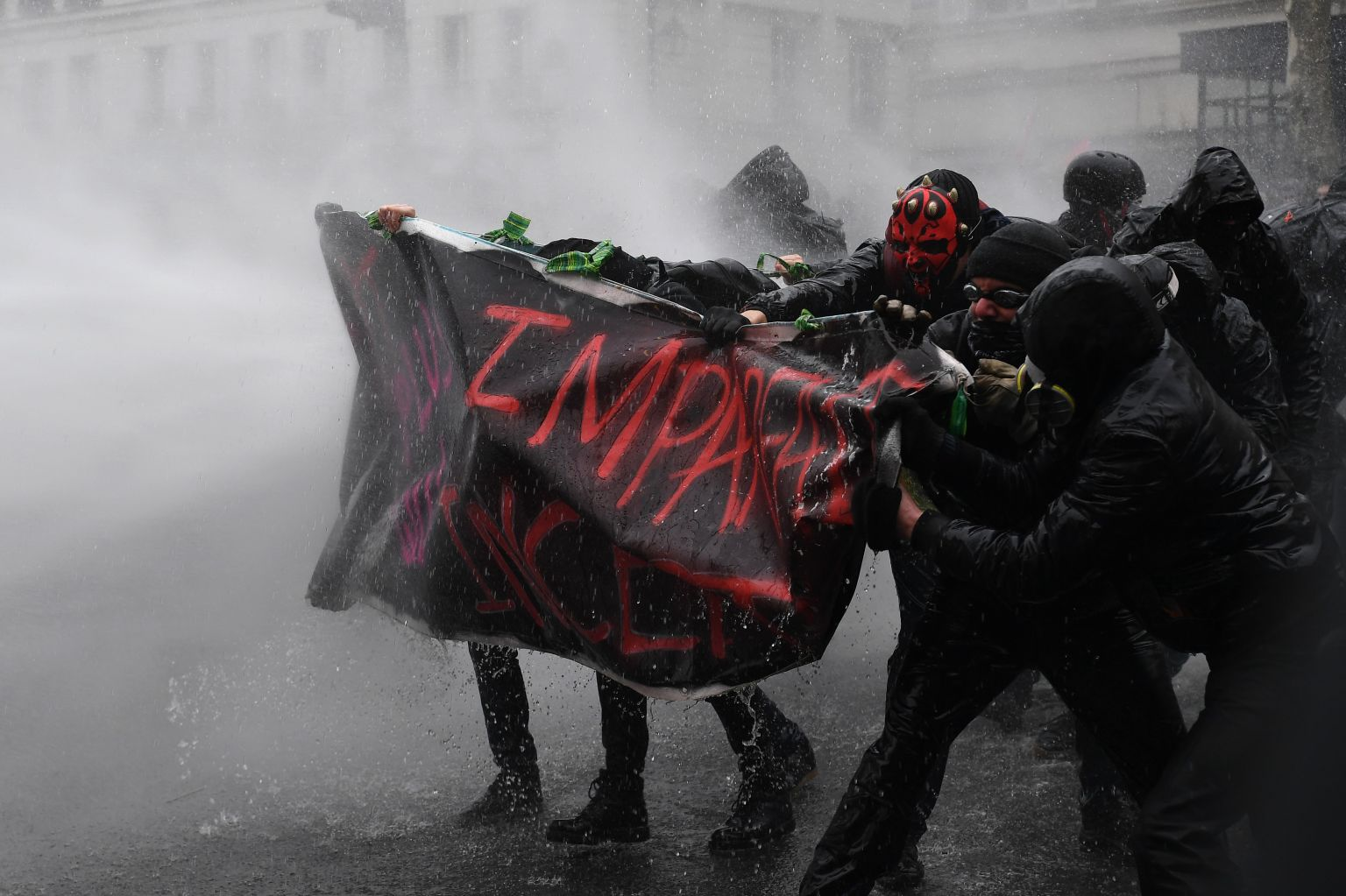 TOPSHOT - Police uses a water canon against demonstrators during a protest against French government's string of reforms, on March 22, 2018 in Paris. Seven trade unions have called on public sector workers to strike on March 22, including school and hospital staff, civil servants and air traffic controllers. More than 140 protests are planned across France, the biggest culminating at the Bastille monument in Paris where unions expect 25,000 demonstrators.  / AFP PHOTO / CHRISTOPHE ARCHAMBAULT        (Photo credit should read CHRISTOPHE ARCHAMBAULT/AFP/Getty Images)