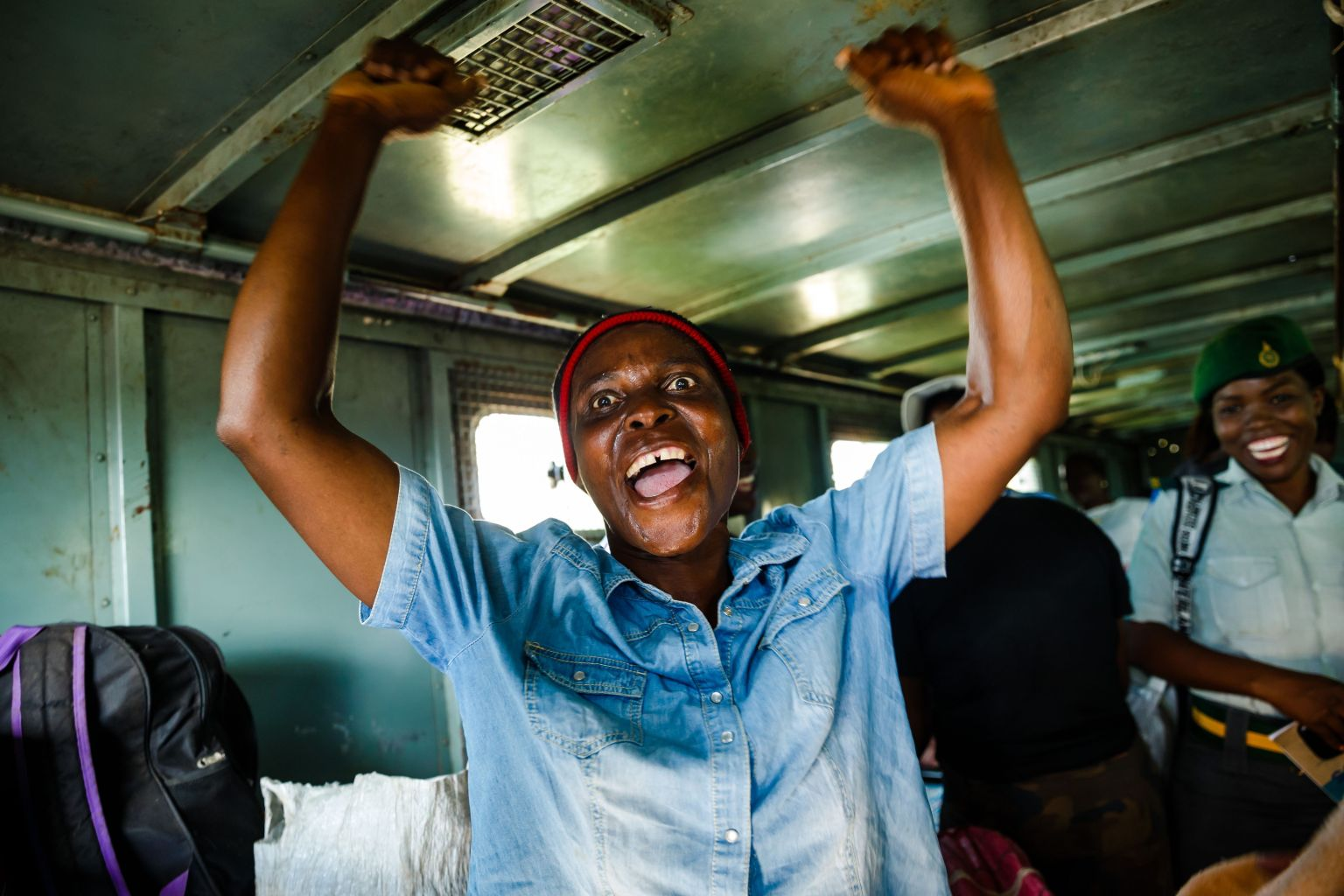 TOPSHOT - Female prisoners celebrate with songs in the back of a prison's truck as she is released from the Chikurubi Prison, in Harare, on March 22, 2018. Zimbabwean President Emmerson Mnangagwa, who succeeded ousted Robert Mugabe in November, has pardoned at least 3,000 prisoners to clear out overpopulated jails, officials said on March 22 2018. The pardon will see the release of all female prisoners except those serving life terms, as well as all disabled and juvenile prisoners. Terminally-ill prisoners and those above the age of 60 who have served a third of their time will also be freed.   / AFP PHOTO / Jekesai NJIKIZANA        (Photo credit should read JEKESAI NJIKIZANA/AFP/Getty Images)