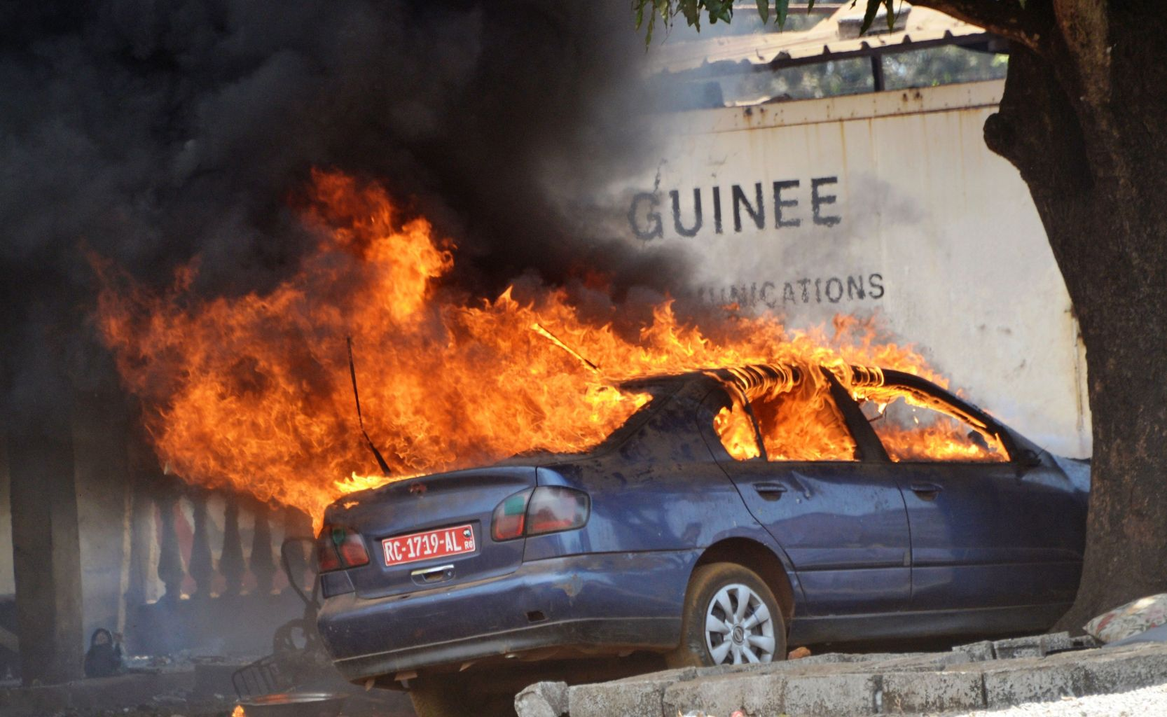 """This photo shows a car on fire in a police station in Conakry as anti-riot police clash with Guinean opposition supporters on March 22, 2018. The police dispersed on March 22 in Conakry a demonstration of the Guinean opposition to demand """"the truth of the polls"""", after February 4 local elections. / AFP PHOTO / CELLOU BINANI        (Photo credit should read CELLOU BINANI/AFP/Getty Images)"""