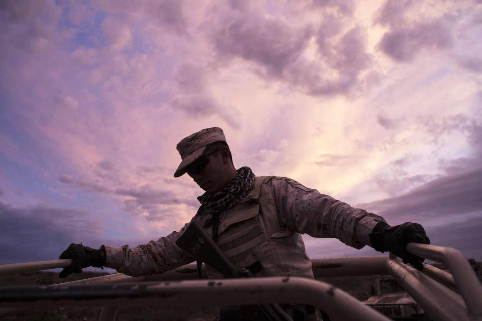 TOPSHOT - The sun sets as a Mexican soldier rides his vehicle after destroying illegal marijuana plantations at El Ajusco, near Ensenada, Baja California state, on March 22, 2018, northwestern Mexico. The Mexican Army located four marihuana plantations on March 21 with a total surface of 5,600 square meters. / AFP PHOTO / GUILLERMO ARIAS        (Photo credit should read GUILLERMO ARIAS/AFP/Getty Images)
