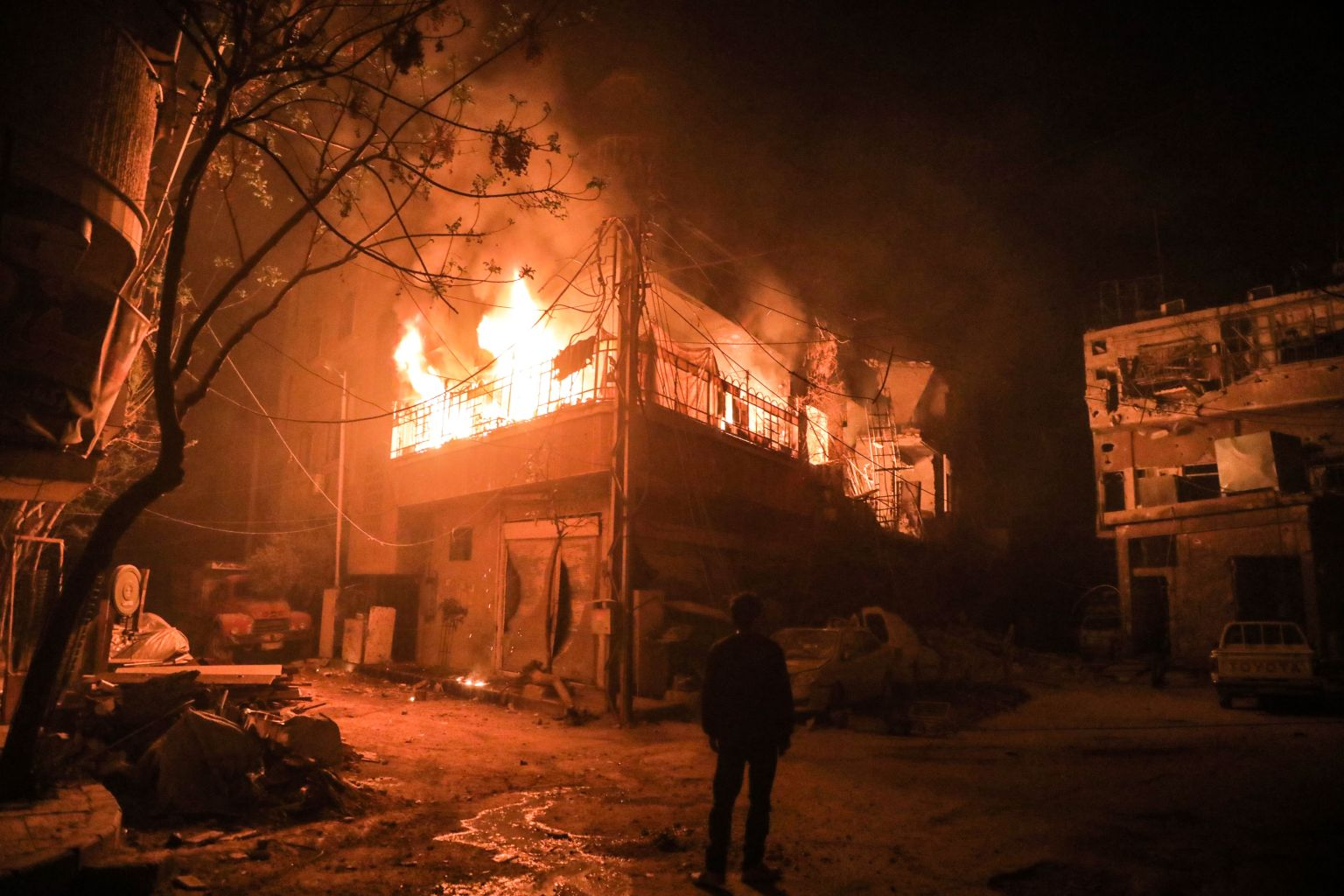 TOPSHOT - A picture taken early on March 23, 2018 shows a man standing looking at flames erupting in a building following regime bombardment in Douma, one of the few remaining rebel-held pockets in Eastern Ghouta on the outskirts of the capital Damascus. / AFP PHOTO / HAMZA AL-AJWEH        (Photo credit should read HAMZA AL-AJWEH/AFP/Getty Images)
