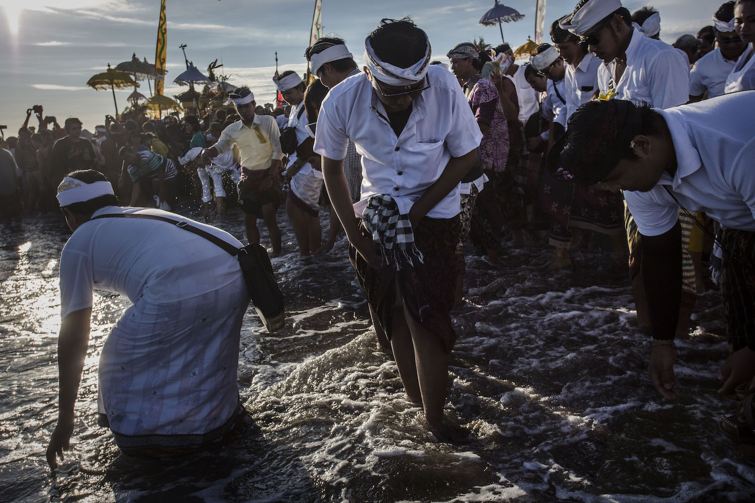 Hindu devotees prepare wash their faces with sea water as they pray during the Melasti ritual ceremony at Parangkusumo beach on March 11, 2018 in Yogyakarta, Indonesia.The Melasti ritual is held annually ahead of the Nyepi Day of Silence, a ceremony intended to cleanse and purify the souls of the Balinese Hindu participants. Nyepi is a Hindu celebration observed every new year according to the Balinese calendar. The national holiday is one of self-reflection and meditation and activities such as working, watching television or travelling are restricted between the hours of 6 a.m. and 6 p.m. (Photo by Ulet Ifansasti/Getty Images)