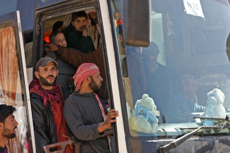 Syrian civilians and rebel fighters stand in a bus  on March 26, 2018, after their evacuation from Eastern Ghouta.