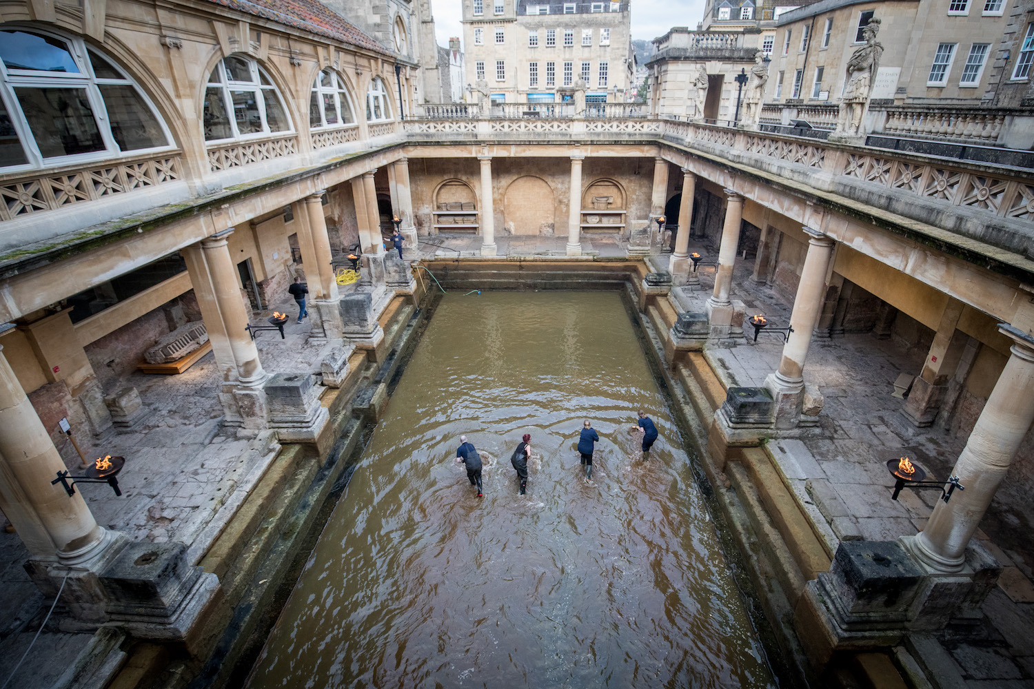 Bath and North East Somerset Council employees brush algae and sludge from the original Roman lead lined floor of the Great Bath as it is drained of 250,000 litres of hot natural thermae spa water as part of a spring cleaning operation, at the historic Roman Baths on March 27, 2018 in Bath, England. Previous cleaning operations, which has to be done regularly to prevent the normally 1.6 metres (5ft) deep baths from becoming murky and to stop algae from growing, have revealed all manners of modern day debris including traffic cones, shopping trolleys and even a moped. Sited below modern street level the Roman Baths built in AD76 and which take water from Britain's largest thermal spring, contains one of the best examples of a preserved Roman bath complex in Europe. Accidentally re-discovered in the 1800s, the steps and lead lining of the Great Bath are over 2000 years old and are visited by over one million tourists a year.  (Photo by Matt Cardy/Getty Images)