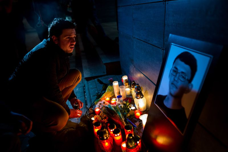 A man lights a candle in front of the Aktuality newsroom, the employer of the murdered investigative journalist Jan Kuciak, in Bratislava.