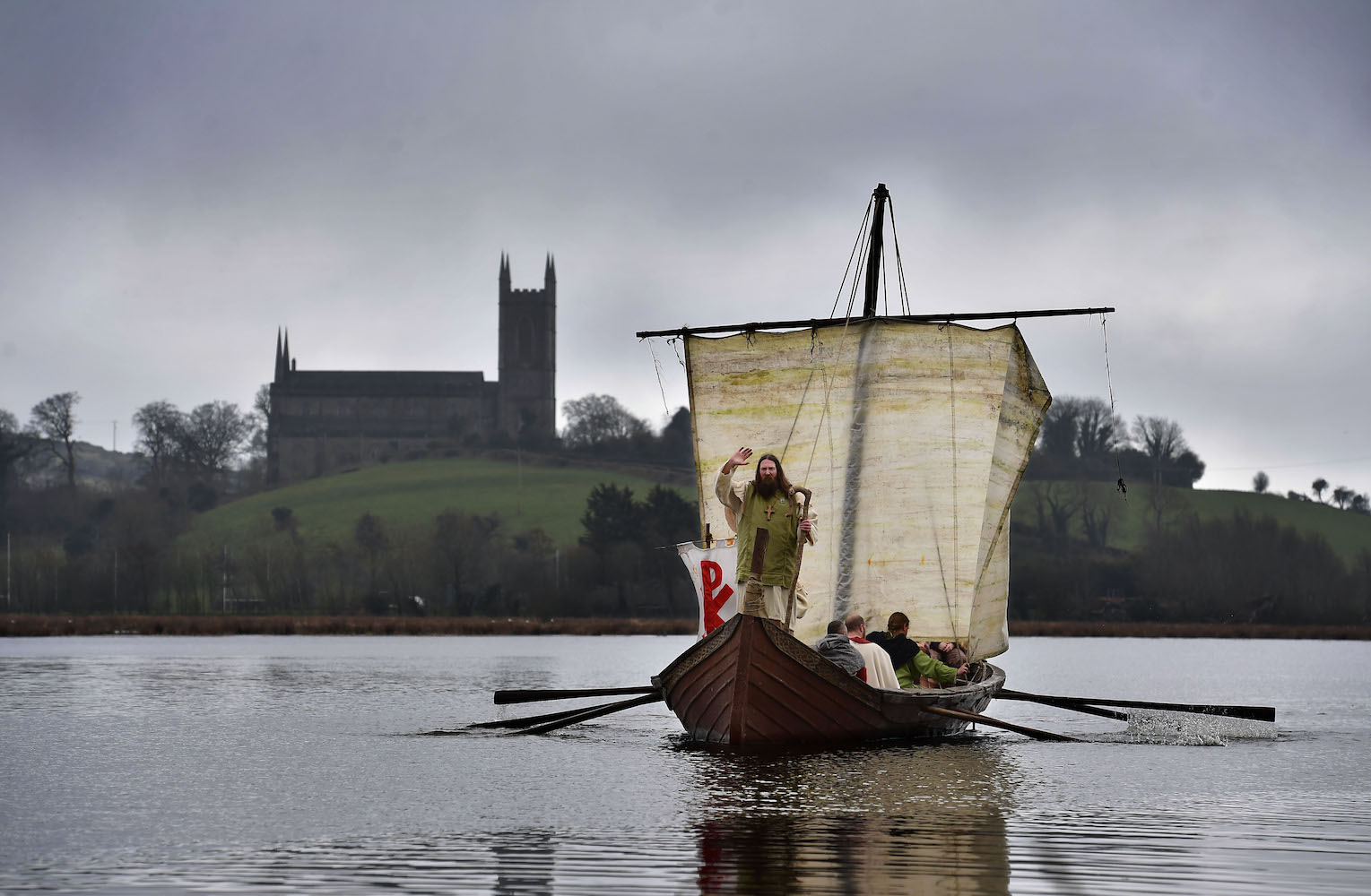 DOWNPATRICK, NORTHERN IRELAND - MARCH 11: Marty Burns who plays Saint Patrick is brought to shore past Downpatrick cathedral as the re-enactment of Saint Patrick's first landing in Ireland takes place at Inch Abbey on March 11, 2018 in Downpatrick, Northern Ireland. The Irish annals for the fifth century date Patrick's arrival in Ireland in the year 432. The patron saint of Ireland's remains are believed to be buried at Down Cathedral. Saint Patrick's Day is celebrated on the 17th of March. (Photo by Charles McQuillan/Getty Images)