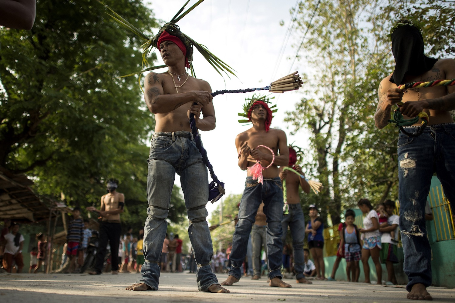Flagellant RJ Rivera (front L) whips his back with bamboo before being wounded to bleed as part of his penitence during the re-enactment of the crucifixion of Jesus Christ for Good Friday celebrations ahead of Easter in the village of San Juan, Pampanga, north of Manila on March 30, 2018.  Rivera, a 33-year-old construction worker, has been a flagellant for 11 straight years and said he does it for the sake of his wife, who is working in Saudi Arabia, and his two daughters and son. / AFP PHOTO / Noel CELIS        (Photo credit should read NOEL CELIS/AFP/Getty Images)