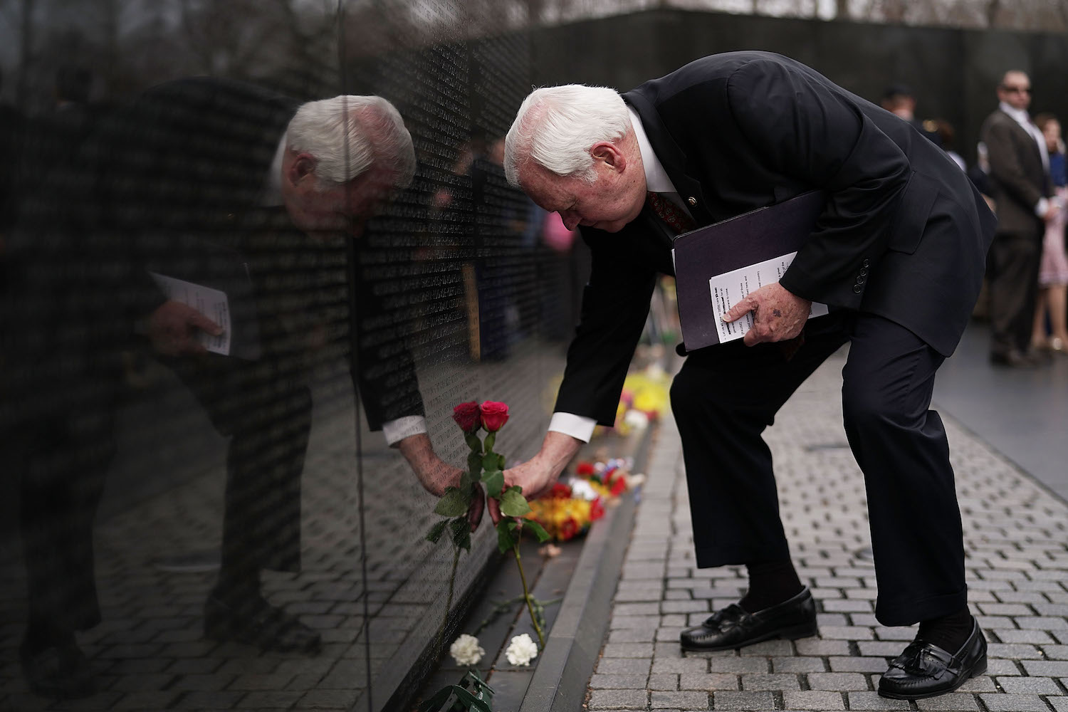 U.S. Deputy Secretary of Veterans Affairs Thomas Bowman lays a rose at the Vietnam War Memorial March 29, in Washington, DC. (Alex Wong/Getty Images)