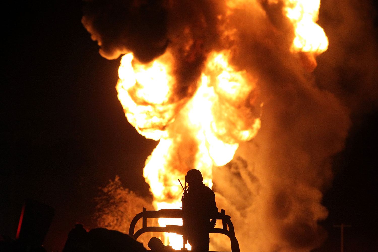 A Mexican soldier stands guard while workers of the state-owned oil company Pemex and local firefighters work to control a fire believed to have started in a pipeline due to fuel-theft activity in the community of San Sebastianito on April 3. Fuel theft is becoming more common every year in Mexico as drug cartels and other gangs diversify their illegal activities. Thousands of illegal taps were discovered in pipelines in recent years. (Ulises Ruiz/AFP/Getty Images)