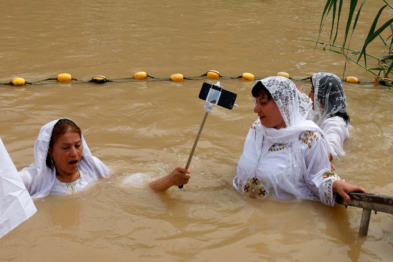 A Coptic Egyptian pilgrim holds a selfie stick as she submerges herself in the waters of the Jordan River on April 3 at the Qasr al-Yahud baptismal site near the West Bank city of Jericho during their Easter pilgrimage to the Holy Land. According to the gospels, Jesus Christ was baptized in the waters of the Jordan River by John the Baptist. (Gali Tibbon/AFP/Getty Images)