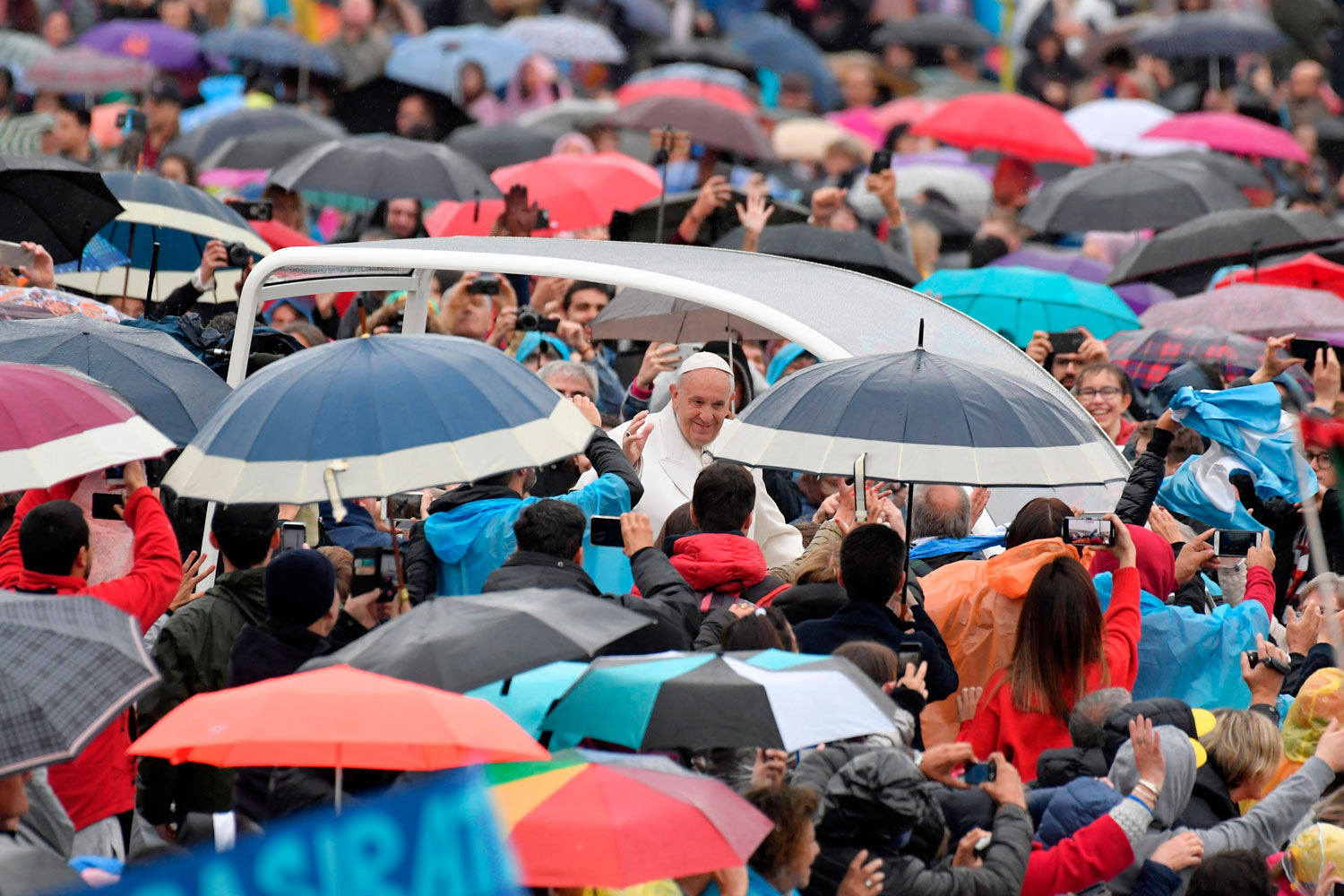 Pope Francis greets the crowd in the rain as he arrives for a weekly general audience at St. Peter's Square on April 4 in Vatican City. (Tiziana Fabi/AFP/Getty Images)