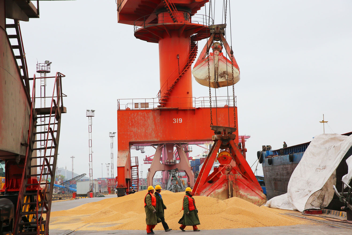 Workers walk past imported soybeans at a port in Nantong in China's eastern Jiangsu province on April 4. China unveiled plans to hit major U.S. exports —  such as soybeans, cars and small airplanes — with retaliatory tariffs worth $50 billion in an escalating trade duel between the world's top economies. (AFP/Getty Images)