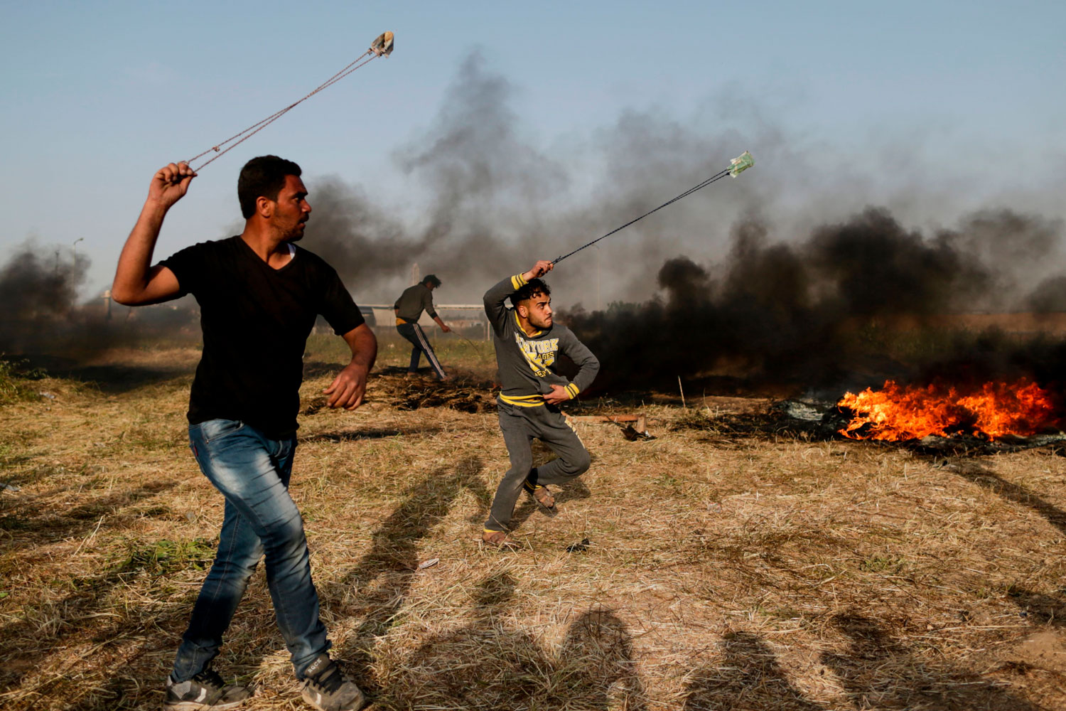 Palestinian protesters use slingshots to throw stones toward Israeli forces at the Israel-Gaza border east of Gaza City on April 4. Hundreds of Palestinian youth have set up a tent city closer to the border than in recent years, hurling stones and rolling burning tires at Israeli soldiers. The protests come on the heels of last week's deadly border demonstration in which soldiers killed 19 Palestinians. (Mahmud Hams/AFP/Getty Images)