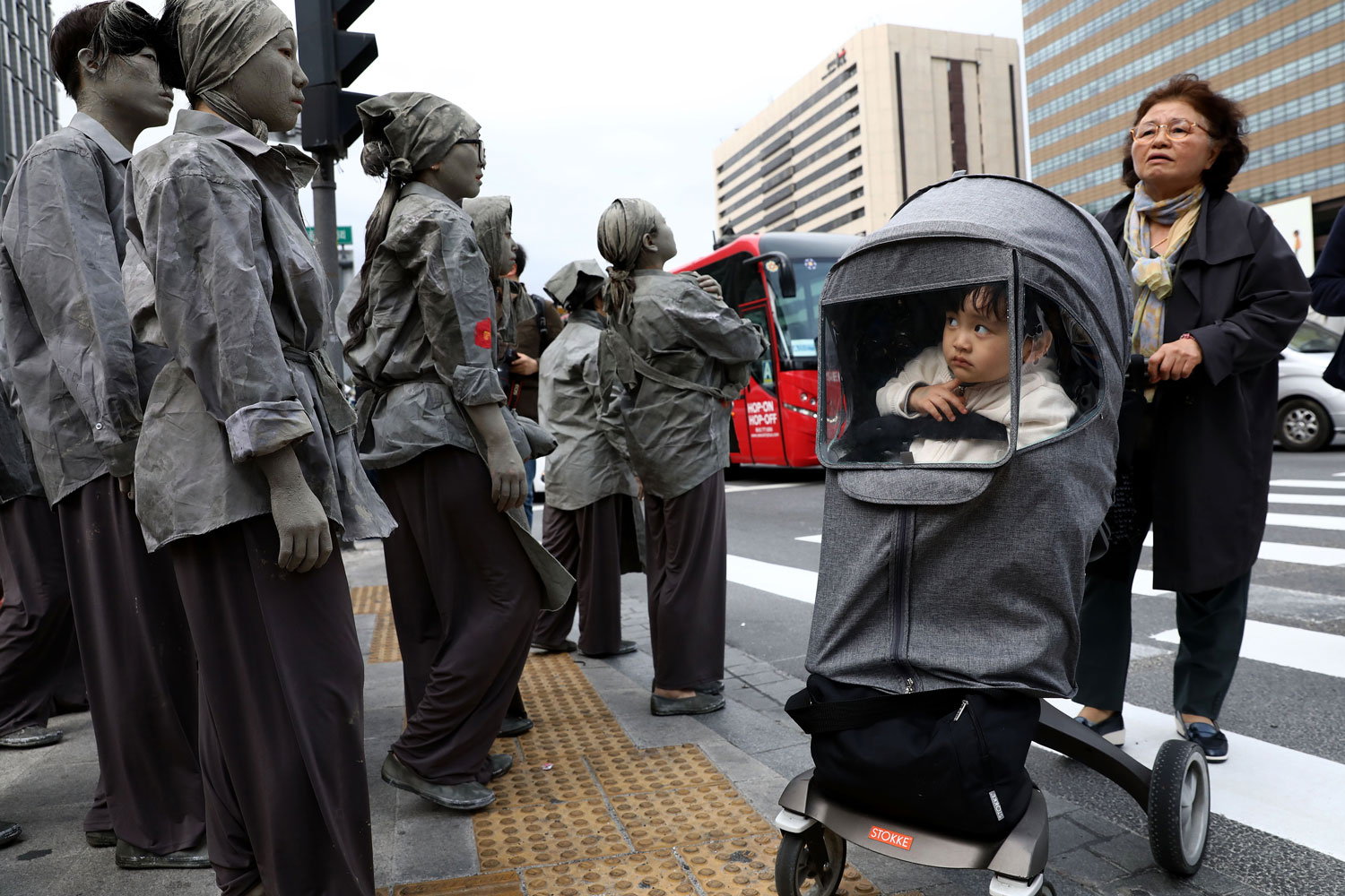 A boy peers at South Korean performers during the 70th anniversary commemoration of the Jeju Uprising on April 3 in Seoul. About 300 people took part in the performance to pay respect to victims of the clash between South Korean government under the control of United Nation Temporary Commission on Korea and the guerrilla fighters of the South Korean Labor Party, which was ruling the island in 1948. Tens of thousands of people are said to have been killed. (Chung Sung-Jun/Getty Images)