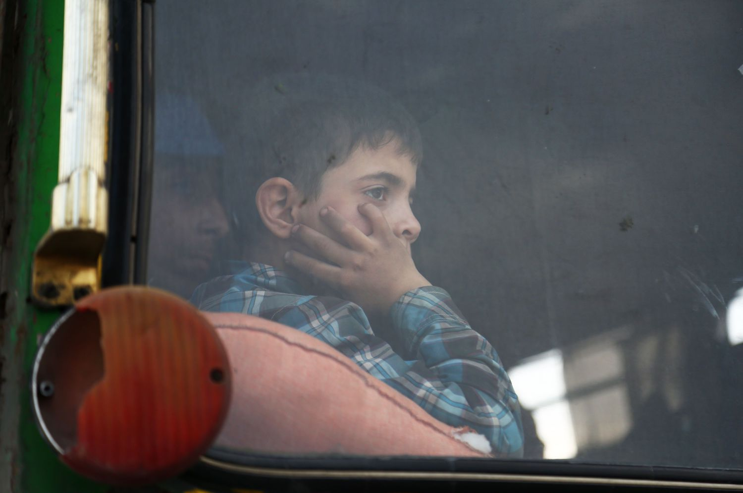 A child looks out of the window as buses carrying Jaish al-Islam fighters and their families from their former rebel bastion of Douma, arrive at the Abu al-Zindeen checkpoint controlled by Turkish-backed rebel fighters near the northern Syrian town of al-Bab, on April 12, 2018. Rebels in Syria's Eastern Ghouta surrendered their heavy weapons and their leader left the enclave, a monitor said, signalling the end of one of the bloodiest assaults of Syria's seven-year war. / AFP PHOTO / Nazeer al-Khatib        (Photo credit should read NAZEER AL-KHATIB/AFP/Getty Images)