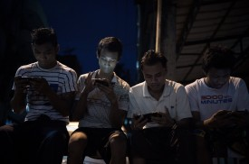 Young men browse Facebook on a street in Yangon, Myanmar, on Aug. 20, 2015. (Nicolas Asfouri/AFP/Getty Images)