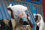 Sudanese workers unload an aid shipment organized by the United States Agency for International Development and the World Food Programme in Port Sudan on May 5, 2016. (Ashraf Shazly/AFP/Getty Images)