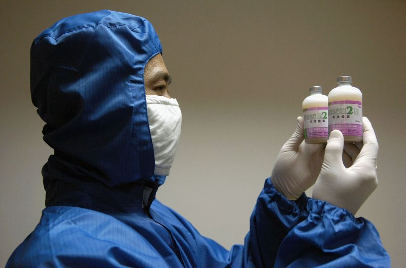 A lab worker in China displays the newly developed Inactivated Vaccine for Streptococcal Disease (Type 2) in Swine at Guangdong Winsun Bio Pharmaceutical Co. Ltd on July 31, 2005 in Guangzhou, Guangdong Province, China. (China Photos/Getty Images)