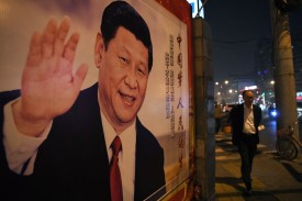 A man walks past a roadside poster of Chinese President Xi Jinping in Beijing, on Oct. 24, 2017. (Greg Baker/AFP/Getty Images)