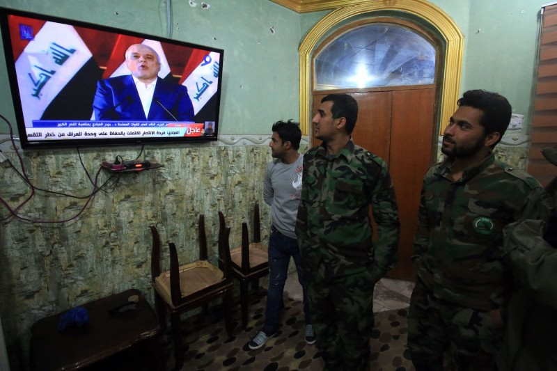 Members of Iraq's Popular Mobilization Forces in the city of Basra watch a televised statement by Iraqi Prime Minister Haider al-Abadi on Dec. 9, 2017. (Haidar Mohammed Ali/AFP/Getty Images)