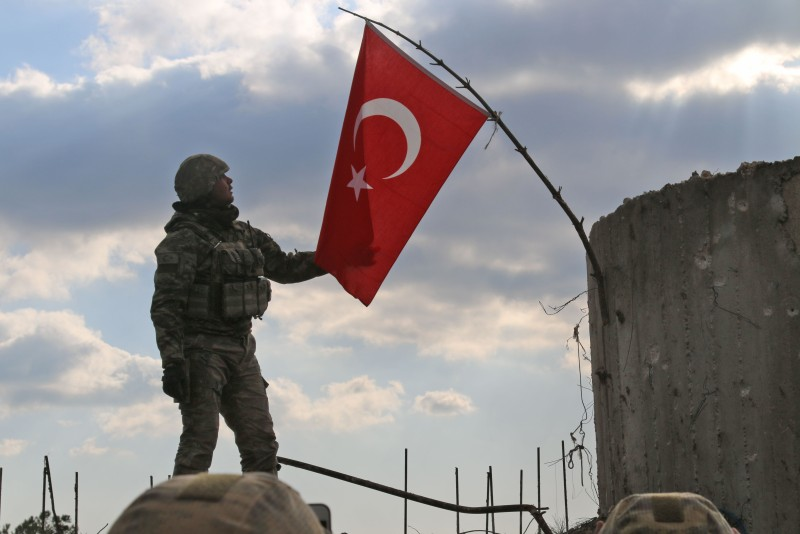 A Turkish soldier checks the national flag on a mountain on the Syrian-Turkish border, north of Azaz on Jan. 28, 2018.(MAAN AL-SHANAN/AFP/Getty Images)