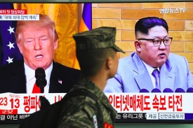 A South Korean soldier walks past a television showing U.S. President Donald Trump and North Korean leader Kim Jong Un at a railway station in Seoul on March 9. (Jung Yeon-je/AFP/Getty Images)