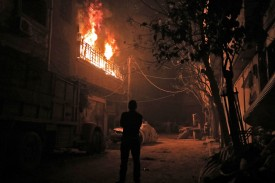 A Syrian man looks at a building fire following regime bombardment in Douma, one of the few remaining rebel-held pockets in Eastern Ghouta, on the outskirts of Damascus on March 23. (Hamza al-Ajweh/AFP/Getty Images)