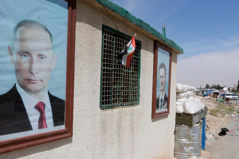 Portraits of the Russian and Syrian presidents are displayed at the government-held Wafideen checkpoint on the outskirts of Damascus on April 3. (Louai Beshara/AFP/Getty Images)