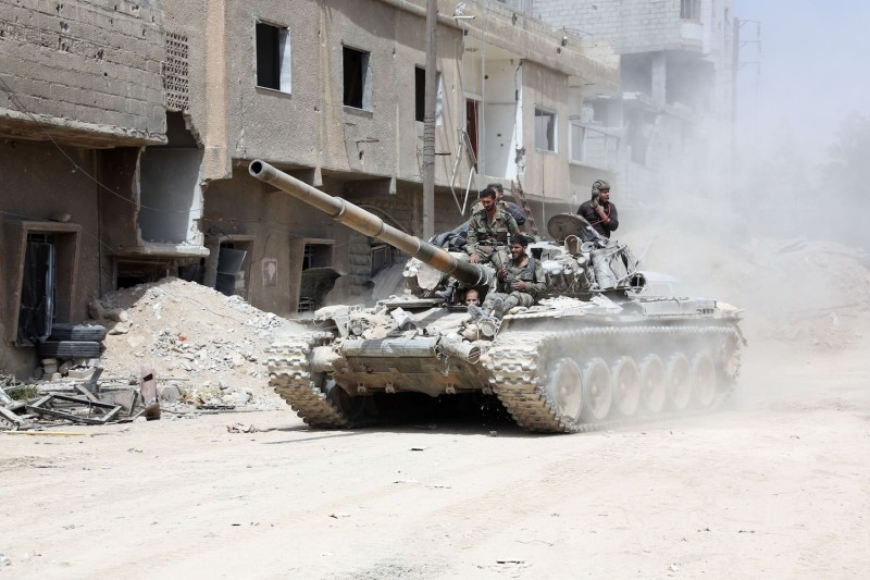 A picture taken on April 8, 2018, shows Syrian Army soldiers advancing in an area on the eastern outskirts of Douma, as they continue their fierce offensive to retake the last opposition holdout in Eastern Ghouta. STRINGER/AFP/Getty Images