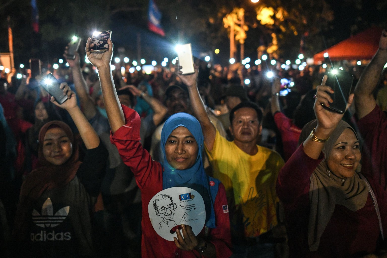 Supporters turn on flashlights on their phones in celebration April 15 after former Malaysian Prime Minister Mahathir Mohamad was selected as Langkawi parliamentary constituency candidate during a rally ahead of the general election. MOHD RASFAN/AFP/Getty Images