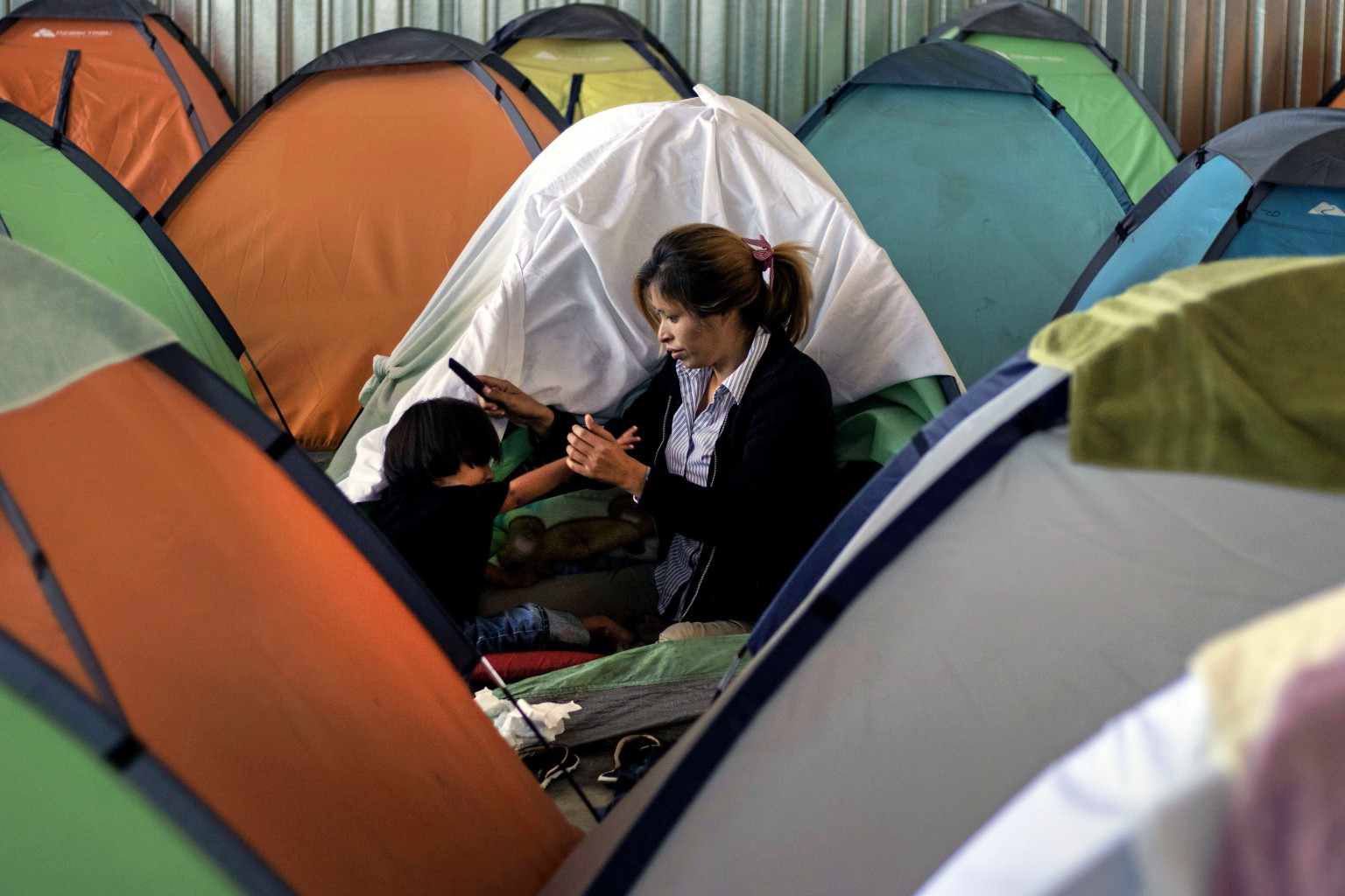 Elsa, a Central American migrant, combs her daughter Adriana's hair outside their tent at a shelter in Tijuana, Mexico, on April 17. The family was taking part in the annual Stations of the Cross caravan, which has brought awareness to the plight of Central American migrants fleeing violence in their countries. GUILLERMO ARIAS/AFP/Getty Images