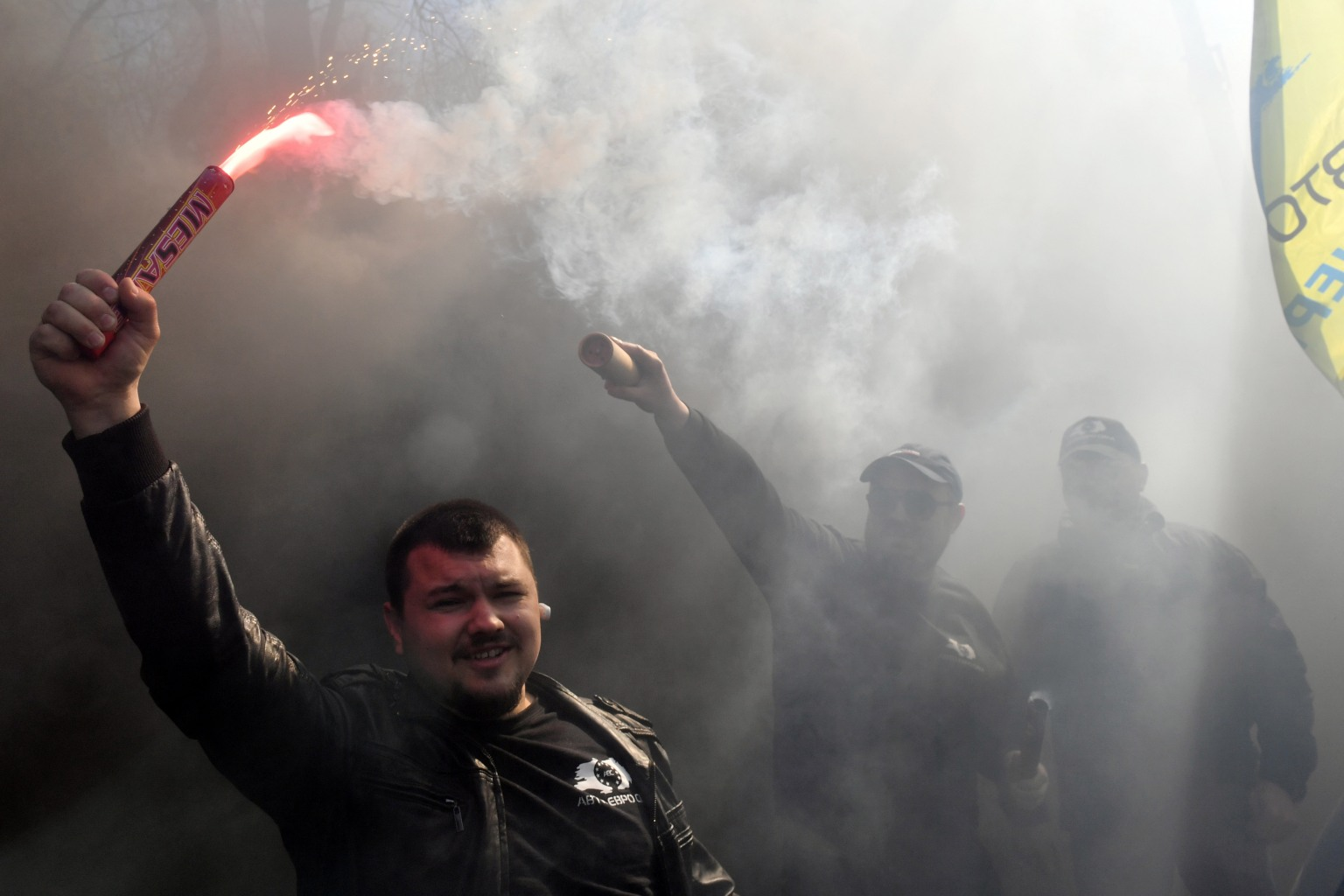 A protester holds a burning smoke bomb as he takes part in a demonstration by AutoEuroPower movement activists near the Ukrainian Cabinet building in Kiev on April 18. Activists protested against a possible reduction of gasoline imports initiated by a number of Ukrainian producers and against the increased price of domestic-made gasoline. SERGEI SUPINSKY/AFP/Getty Images