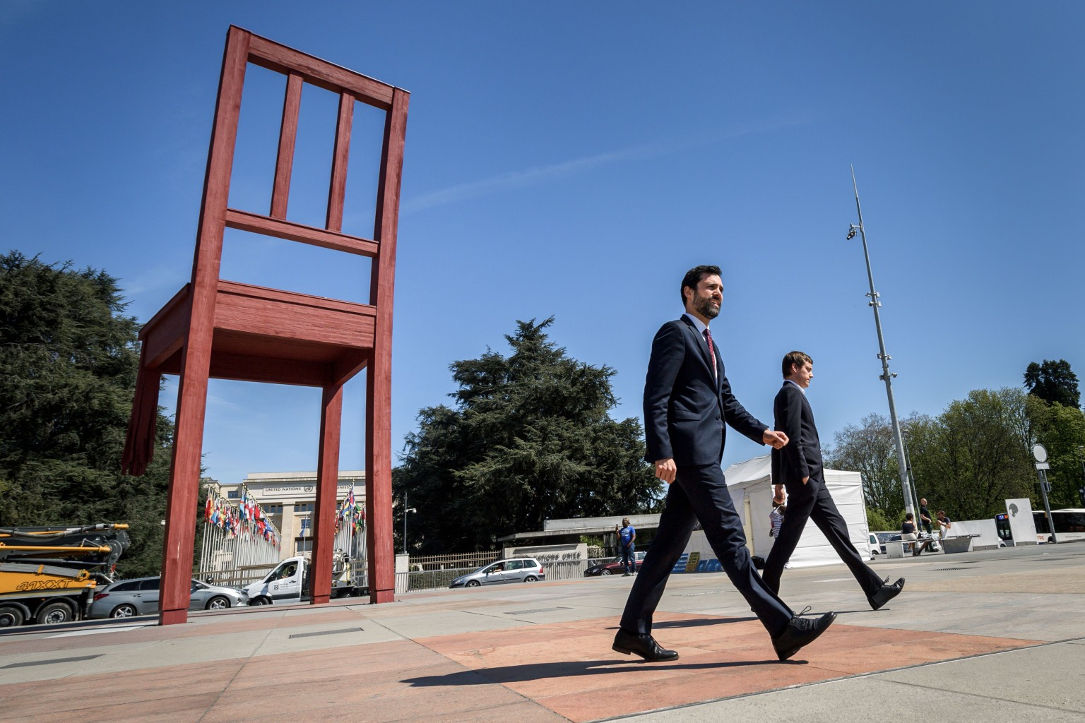 """Catalan Parliament speaker Roger Torrent, left, walks past the Broken Chair sculpture on April 18 as he arrives outside the United Nations offices in Geneva to deliver a statement on the """"violation of fundamental rights"""" in Catalonia. Broken Chair was designed by renowned Swiss sculptor Daniel Berset in 1997 at the request of Handicap International. FABRICE COFFRINI/AFP/Getty Images"""