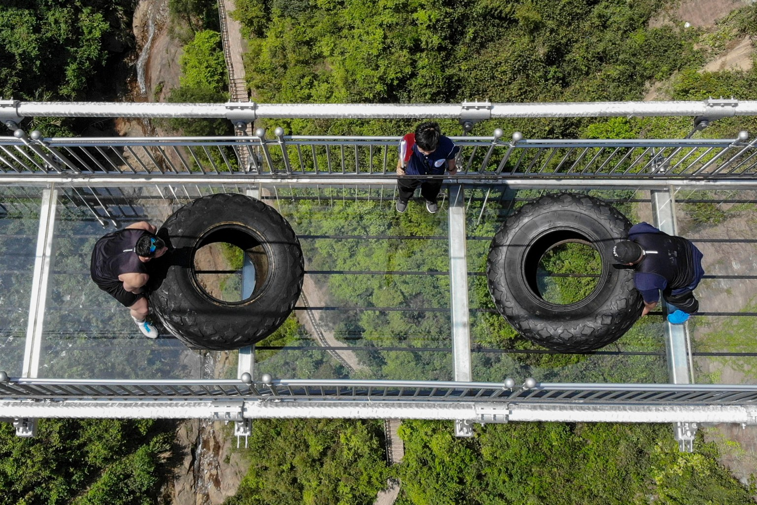 Competitors take part in a tire-flipping competition April 18 on a glass-bottomed bridge in Pingjiang in China's central Hunan province. Contestants flipped 440-pound tires to be the fastest to reach the center of the 984-foot-long bridge. AFP/Getty Images