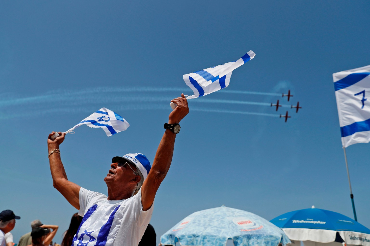 An Israeli takes part in his country's Independence Day on April 19 as planes fly overhead in the Mediterranean coastal city of Tel Aviv. Israel is marking 70 years since the founding of the country according to the Hebrew calendar. AHMAD GHARABLI/AFP/Getty Images